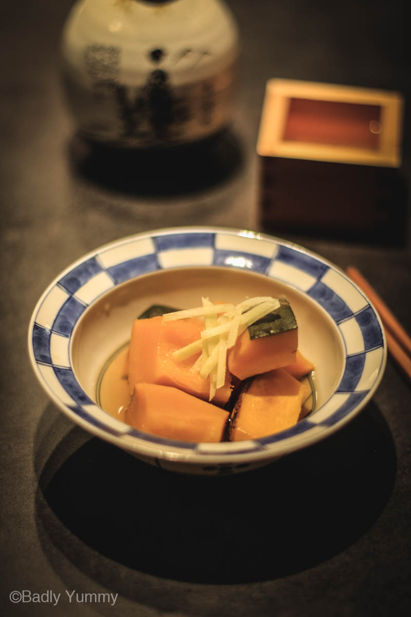 Kabocha simmered with ginger in a small blue and white bowl